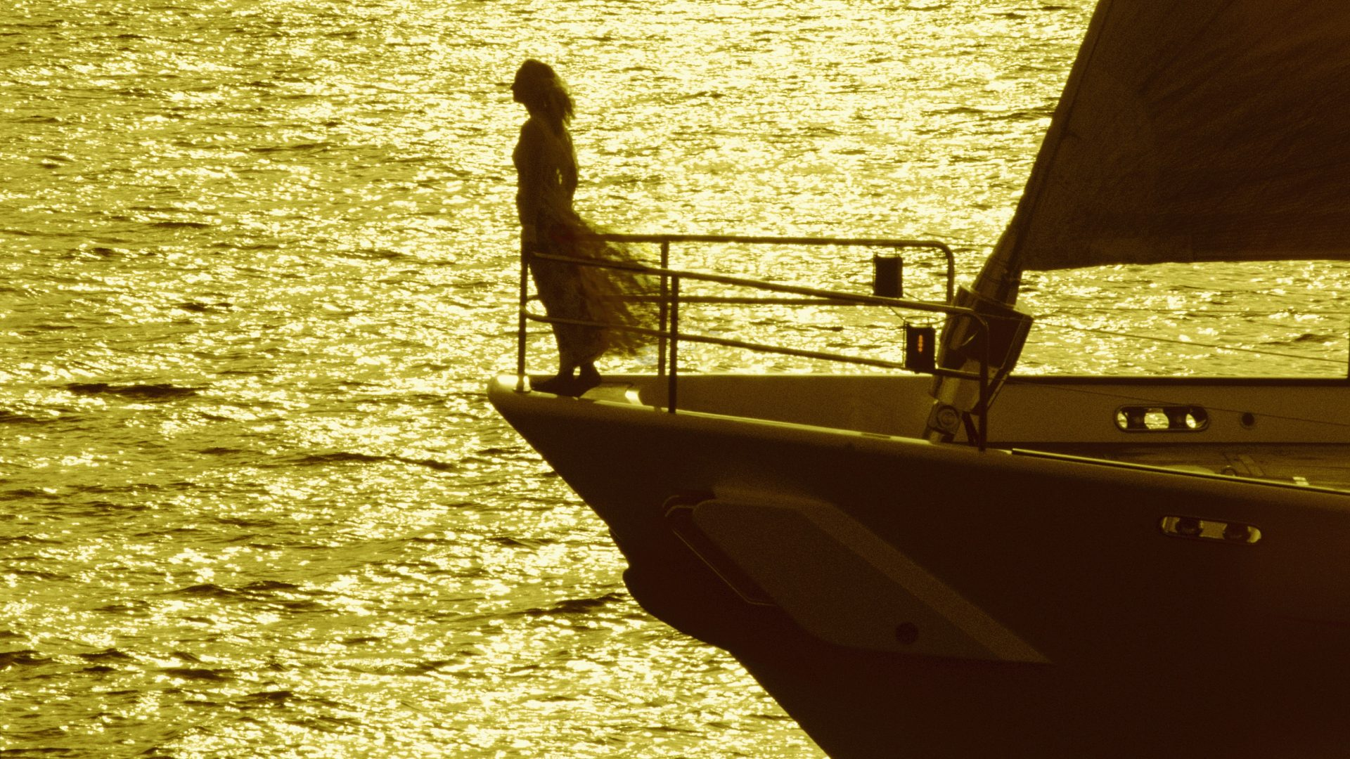 A Woman Stands Silhouetted By Tropical Sun on the Bow of a Superyacht